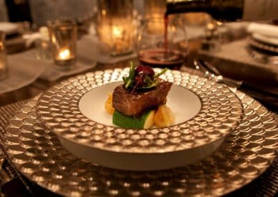 Plated fine dining meal of meat and vegetables on silver trimmed dishware set at a table designed by Patrick Knowles