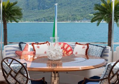 Tropical fabrics and pillows accessorize a dining space on the deck of a Patrick Knowles Designed yacht