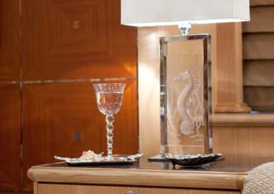 Glass lamp with a frosted glass seahorse on a sleek bed stand next to a crystal glass on a tray