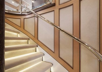 Cream and neutral colored stairway with under step lighting and wood and fabric wall panels in a Patrick Knowles Designed space