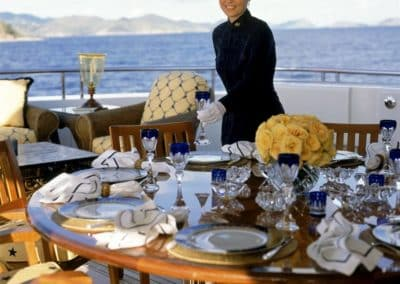 Tablescape designed by Patrick Knowles with blue and clear crystal glassware as a feature and a yellow rose centerpiece with a yacht stewardess smiling as she sets the table in white gloves