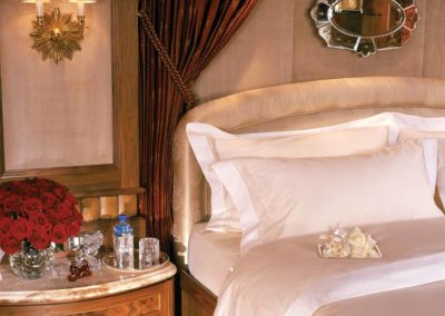 Detail image of a master suite on a superyacht designed by Patrick Knowles with white sheets, red roses on the bedside and a wood and dark mahogany tone