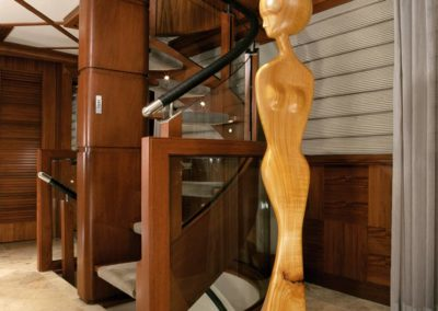 Wood carved sculpture of a woman standing over 6 feet tall in the foyer of a yacht salon designed by Patrick Knowles Designs