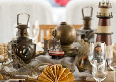 Marine themed tablescape with accessories of lanterns and a miniature lighthouse with a yellow napkin fan folded in the forefront