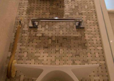 upshot of a shower wall with a basket weave of tile and an architecturally interesting shower stool