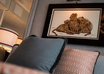Closeup of yacht suite pillows and art work featuring cuddling monkeys
