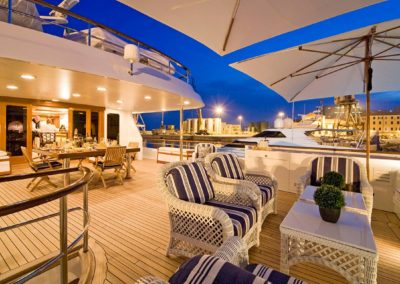 Evening setting on deck of superyacht with seating and dining area designed by Fort Lauderdale yacht designer Patrick Knowles