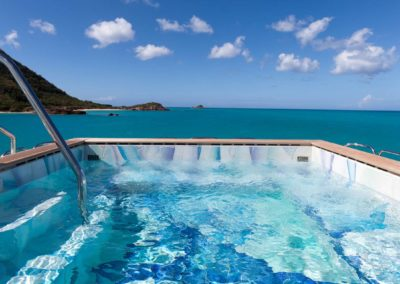 Jacuzzi on deck with beautiful open sea and island of superyacht designed by Fort Lauderdale yacht designer Patrick Knowles