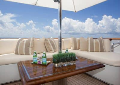 Bright setting of beautiful seating area with table and large umbrella on deck of superyacht designed by Fort Lauderdale yacht designer Patrick Knowles