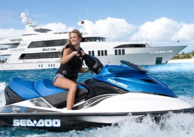 """Woman riding waverunner and superyacht """"Blind Date"""" behind and island in the background designed by Fort Lauderdale yacht designer Patrick Knowles"""
