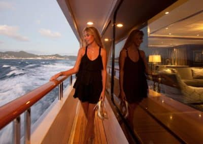 Early evening photograph of beautiful woman and pleasantly lit interior through the window of superyacht in motion designed by Fort Lauderdale based yacht designer Patrick Knowles Designs