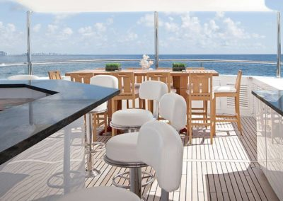 Bar and stools with seating in the back and open sea in the background designed by Fort Lauderdale yacht designer Patrick Knowles