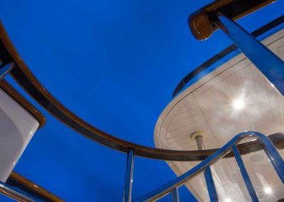 Bottom view of stairway leading to top deck with railing and lights on ceiling designed by Fort Lauderdale yacht designer Patrick Knowles
