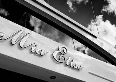 "Close up of superyacht ""Mia Elise"" name with clouds in the background, designed by Fort Lauderdale yacht designer Patrick Knowles"