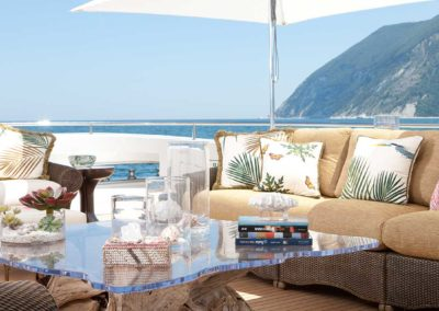 Outdoor seating area with couches and coffee table and a view of a mountain on an island in the background on the top deck of a Superyacht designed by Fort Lauderdale yacht designer Patrick Knowles
