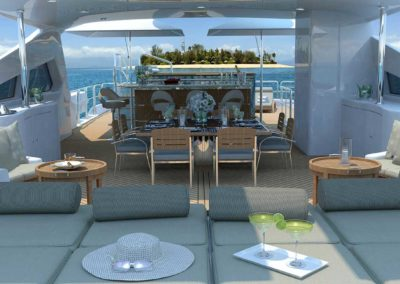 View of chaise lounge chairs with a dining table and an island with open sea all around on the top deck of a superyacht designed by Fort Lauderdale yacht designer Patrick Knowles