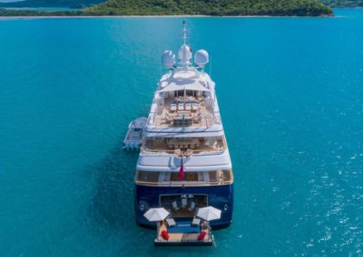 Aerial photo of rear of superyacht with rear deck open on the water, seating area on all decks, designed by Patrick Knowles