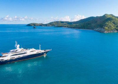 Wide aerial photograph of superyacht and island in the background, designed by Fort Lauderdale yacht designer Patrick Knowles