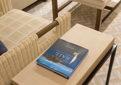 A sailing book on a side table next to a cream colored side chair