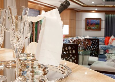 Champagne at the ready with crystal and frosted coral glassware at the forefront with an ocean themed room in the background on a yacht designed by Patrick Knowles