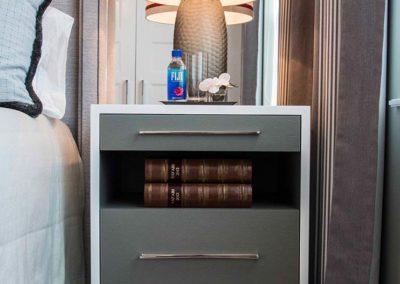 Sleek chic gray side table in bedroom with books and a lamp on the top covered with a red and white lampshade