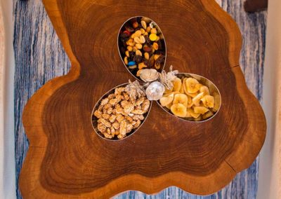 Overview of a natural wood table with a metal candy bowl on top featuring three different treats