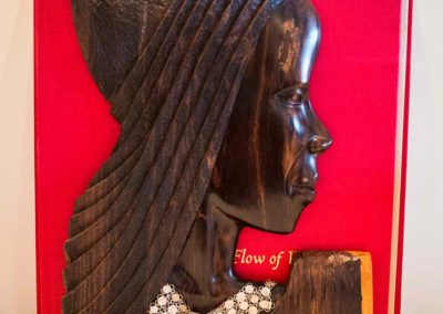 Carved wood bookend designed to look like the profile of a woman
