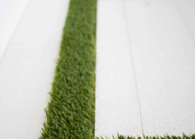 Detail of patio flooring in white wood and grass