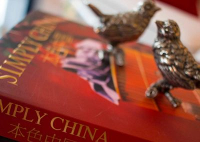 Metal birds on top of a Simply China book as yacht accessories