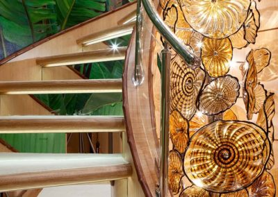 Custom glass lighting against a tropical palm leaf patterned stairway designed by Patrick Knowles yacht interior designer
