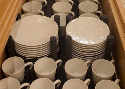Organized mugs and plates in a galley drawer on a superyacht