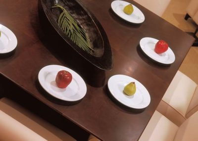 apples and pears tabletop on a dining table with a palm leaf centerpiece