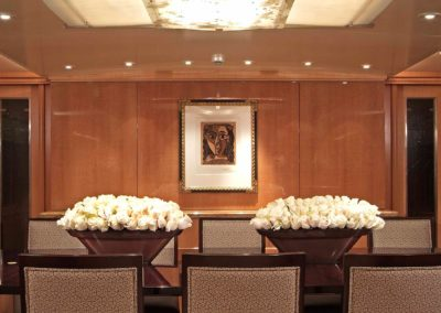 Picasso framed artwork private collection on a superyacht showcased on a polished wood wall on a superyacht in a dining room with bowls of white roses on the table