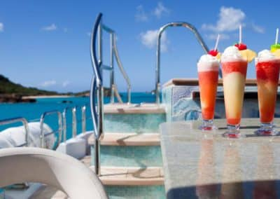 A trio of frozen cocktail drinks on the deck of a Patrick Knowles Designs superyacht with a beautiful backdrop of ocean and mountains