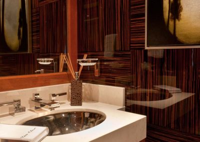 Private yacht head designed by Patrick Knowles Designs with deep wood patterned bathroom walls
