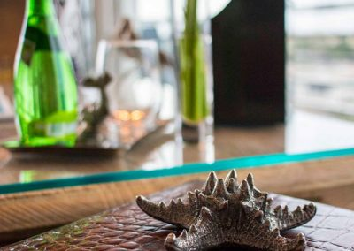 Silver starfish room accessory paperweight on top of a deep brown alligator leather box
