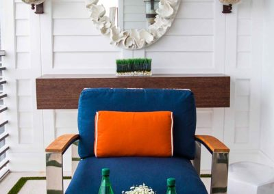 Blue and orange statement chair on a bright white patio in a residential property designed by Patrick Knowles Designs with a chic marine aesthetic