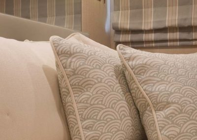 Detail photo of textiles featuring a repeating white and blue scale pattern in a neutral color designed room on a superyacht