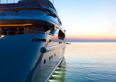Exterior image of a yacht designed by Patrick Knowles on the water at sunset lit from beneath