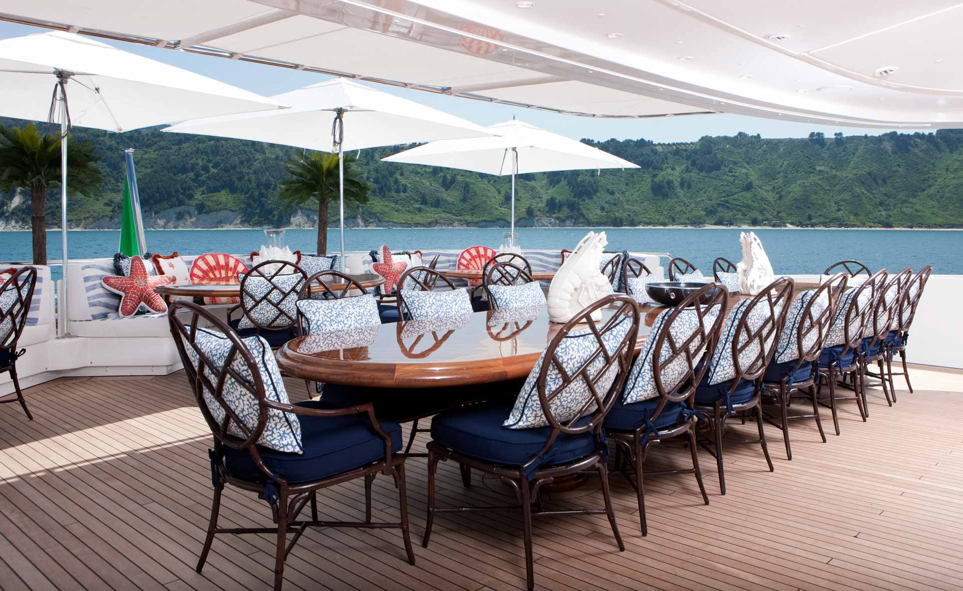 Beautiful dining table on deck covered by large square umbrellas with an island in the background.
